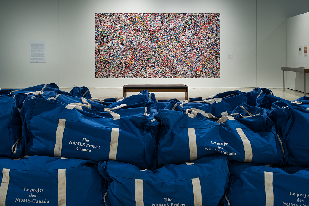 Both images depict Hazel Meyer's installation Container Technologies, created in partnership with the Canadian AIDS Society. The installation comprises 22 Molson Canada blue goalie bags (that contain sections of Canada's AIDS Memorial Quilt) with white straps, each stamped with the phrase 'The Names Project, Canada', and the French translation 'Les projets des NOMS-Canada.' The bags are stacked on top of each other forming two rows and are displayed on a white rectangular platform. The top image offers an installation view of the work in full while the bottom image provides a close-up and detailed view of the installation