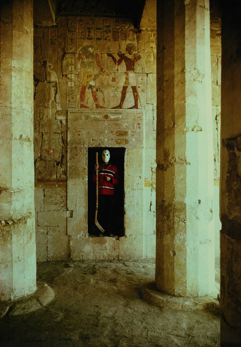 Photograph of a man in a red jersey holding a hockey stick, whose face is completely covered by a traditional white goalie mask with holes for the eyes. The man stands in a rectangular stone cavern inside The Mortuary Temple of Hatshepsut in Egypt.