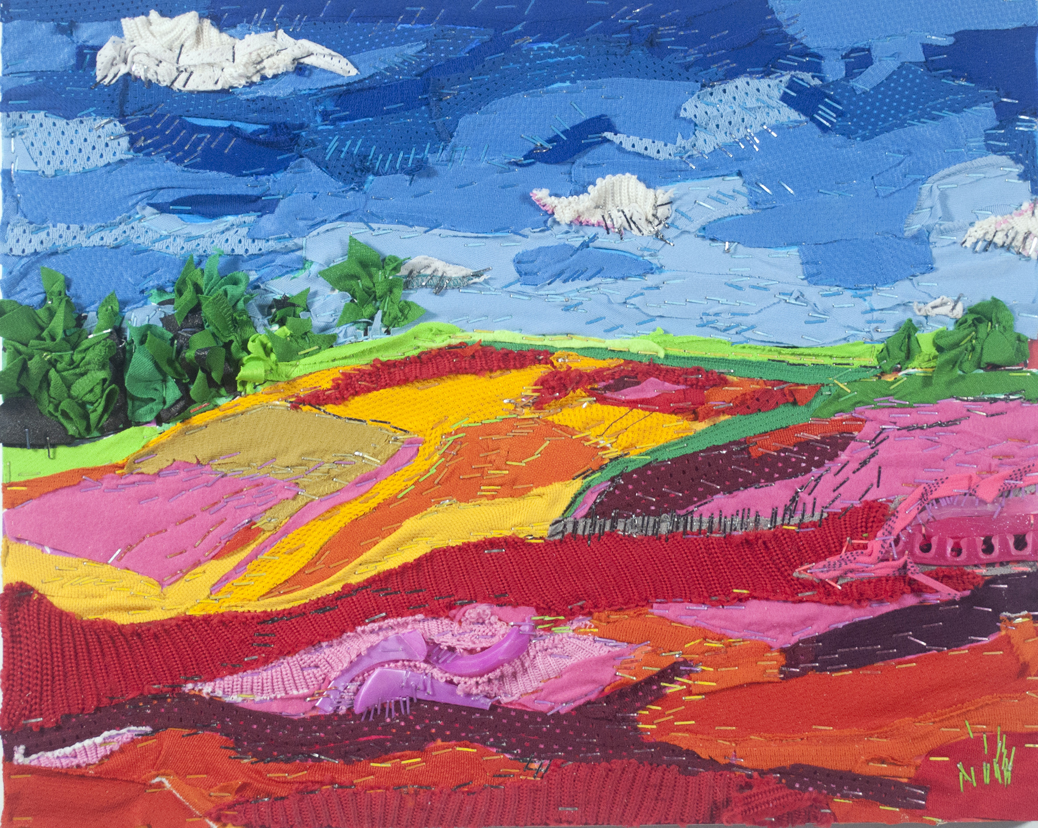 Using recycled hockey equipment, such as shoulder pads, knee pads, jerseys, and hockey sticks, the artist created a large textural collage depicting a spring landscape. There is a blue sky with various layers of dark and light blues, white clouds, a border of forest green trees in the distance as well as trees positioned throughout the landscape, fields of greens, yellows, and blues, and a surrounding fence made of broken hockey sticks.