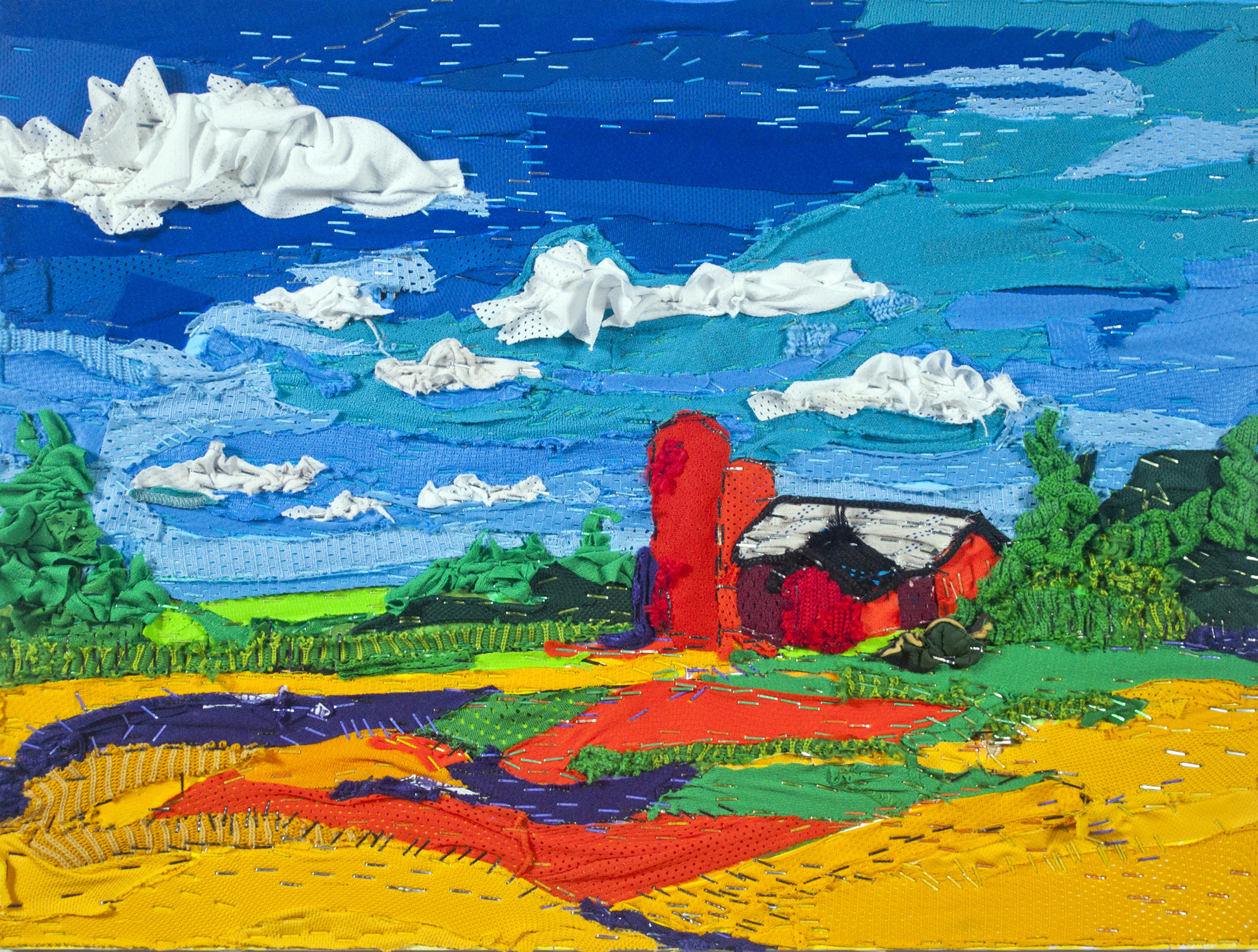 This is a collaged landscape made up of recycled hockey equipment depicting a blue sky with white clouds, trees in full bloom, and red farm sitting on a field of orange, red, and blue hockey jersey fabric. All fabric is stapled to the surface