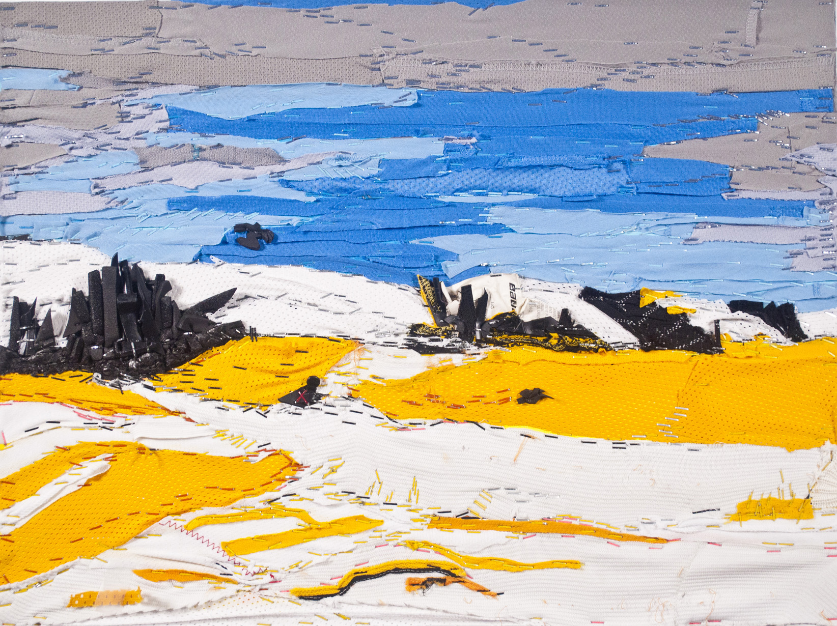 This is a collaged landscape made up of recycled hockey equipment (such as jersey frabric and pad foam) depicting a blue and grey sky with white covered mountains framing black tree trunks and a field of snow with reflections of golden sun rays.