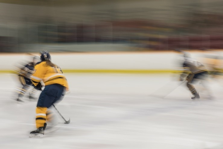 This photograph depicts three women hockey players on the ice, two skating away from the camera and one skating toward. The photo captures movement – the whole image is blurred from the speed of the players whose outlines are visible in yellow and black jerseys. The ice, boards, and audience stands are also blurred in streak-like patterns.