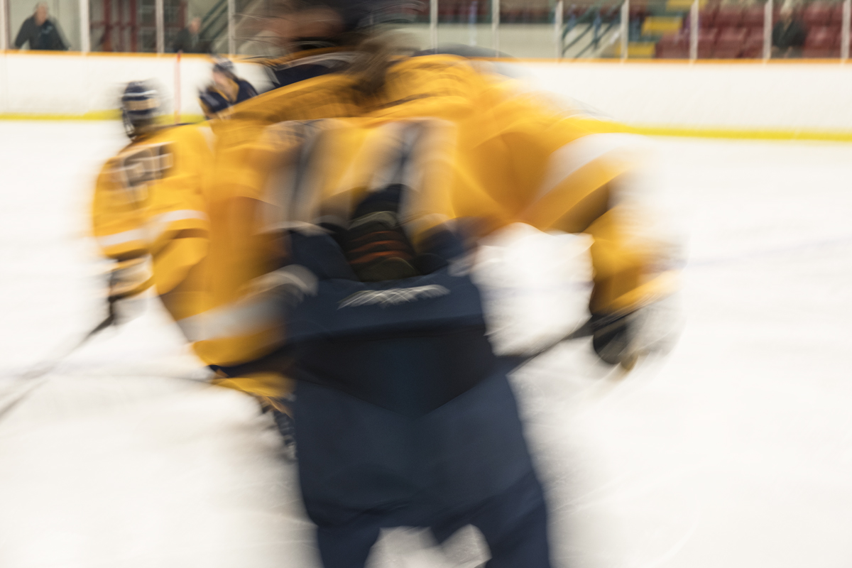 This image captures the backs of two hockey players with yellow jerseys. The first player is centred in the image, the width of their back taking up the middle third of the image, while the second player is barely visible to the left of the main player in the background. This image is especially blurred in all directions, turning both players into gestural figures instead of static or focussed objects.