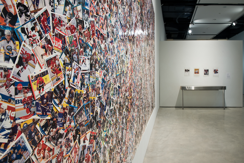Installation photo of collage from an angled perspective. In the foreground, the overlapping hockey cards are visible with predominantly red, yellow, blue, and white colours. The perspective of the image fades toward the background.