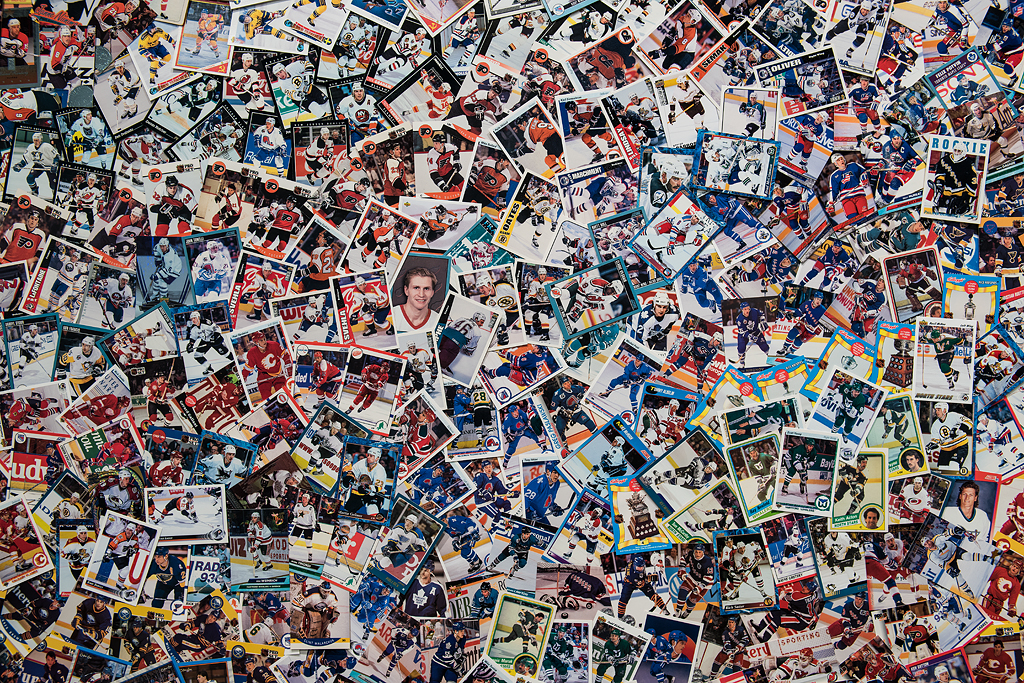 A detail of the large abstract collage fills the frame showcasing hundreds of hockey cards. Here, the cards can be seen as having been laid in a subtle pattern of concentric circles starting from the centre of the image. The cards overlap haphazardly, some images on angles, some upside down. A few images on the cards stick out randomly, like a close-up of a hockey player's face near the centre of the collage, a player celebrating a win near the left of the collage, and a goalie near the right of the collage.