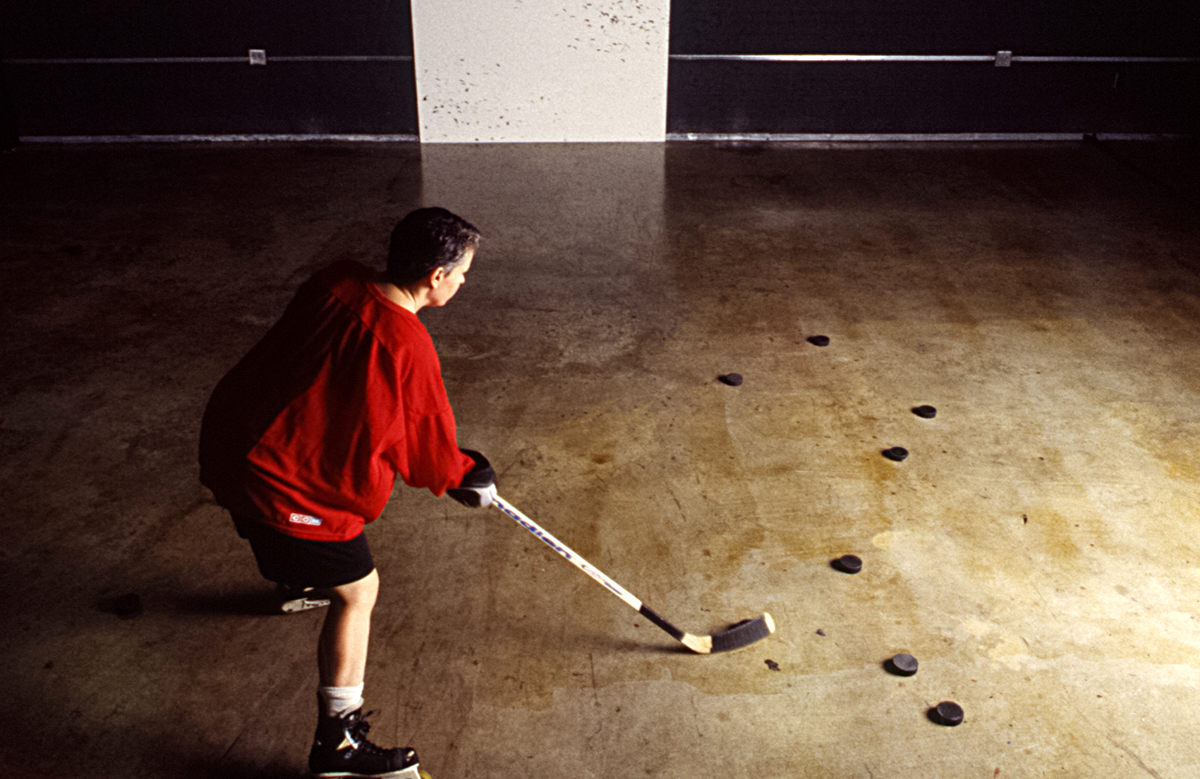 This is a photograph that serves as documentation of the artist's slapshot performance. Wearing their ice skates, black shorts, and a red jersey, Platt is in the act of shooting pucks against a white painted surface.