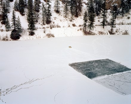 Photograph of a frozen lake in winter, covered in snow, with dark coniferous trees in the background. On the right side of the image there is a rectangular portion of the ice that has been cleared, exposing dark blue ice with faint white markings from skates. A portion of this cleared patch of ice is still covered with a faint dusting of snow. There are faint markings of skate blades in the snow walking toward/away from the cleared ice.