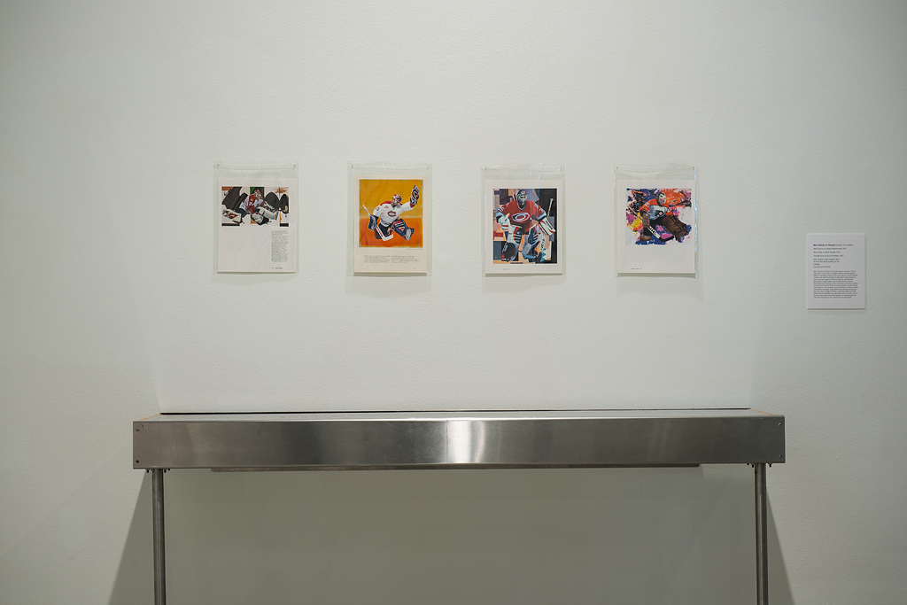 Installation image of four collages of NHL goalies positioned overtop reproductions of abstract paintings by Robert Motherwell, Mark Rothko, and Kurt Schwitters. The four works hang in a horizontal row overtop a display case.