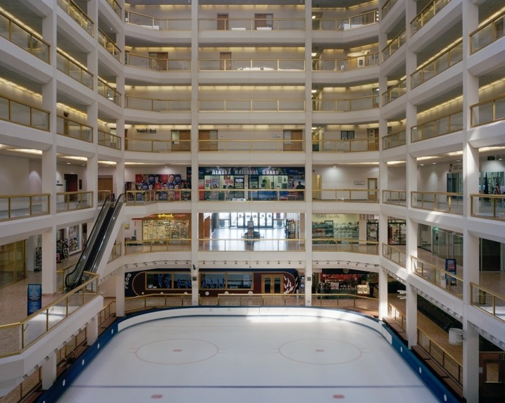 This photograph captures an ice rink in the centre of a shopping mall in Alaska. The mall has at least seven floors with the rink on the bottom floor pictured in the image. Two floors up from the rink is a shop front that says Alaska National Guard. Above this store, the other floors remain non-descript. There are no people in the image, and the rink is empty.