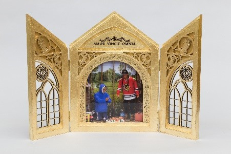 Gold-leafed and ornate birch French doors open to reveal a decolonized nativity scene. Surrounding a baby laying on a Hudson Bay Company's stripped blanket are two men resembling the artist: wearing a blue hooded sweater, the man on the left is kneeling in prayer while the man on the right stands upright in a Chicago Blackhawks hockey jersey. Surrounding objects include a bottle of Coca Cola, bottles of water, non-perishable food items, such as Carnation Evaporated Milk, Campbell's tomato soup, and Spam, a red gasoline can, and what appears to be a beaver pelt. Behind the nativity scene is a painted landscape in which a child is being taken away to residential school. Atop the archway are the words 'Amor Vincit Omnia' – meaning love conquers all.