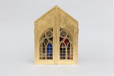 This is an image of the wooden church-like panel with the French doors closed. The front of the panel shows the meeting of the two doors with carvings resembling stained glass. Through these carved windows, the scene of the men and trees is faintly visible.
