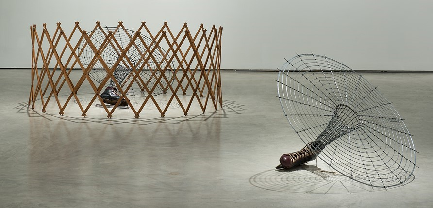 Sculptural installation comprising two parts. On the left side of the image is a large antique wooden expandable accordion circle baby gate. Inside the gate is a single men's ice skate positioned on the side. Attached to the skate is a metal leg-like armature that grows out at the knee to form a large circular spider web-like grid. To the right of the accordion gated skate is a second men's ice skate attached to a similar leg armature and web-like form leaning to the side