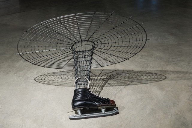 Close-up image (from a different angle) of one of the men's ice skates with the armature and web-like grid leaning on its side