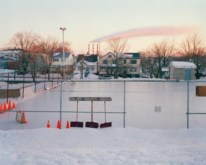 This photograph captures a smooth, homemade ice rink in the middle of a neighborhood which is currently empty and still. The rink is surrounded by chain link metal fencing, and there are bright orange pilons on the left foreground corner of the rink. In the background are houses with rooftops gently covered with snow. One long fuzzy cloud streaks across the sky, coloured with pale yellow, orange, and blue as the sun rises.