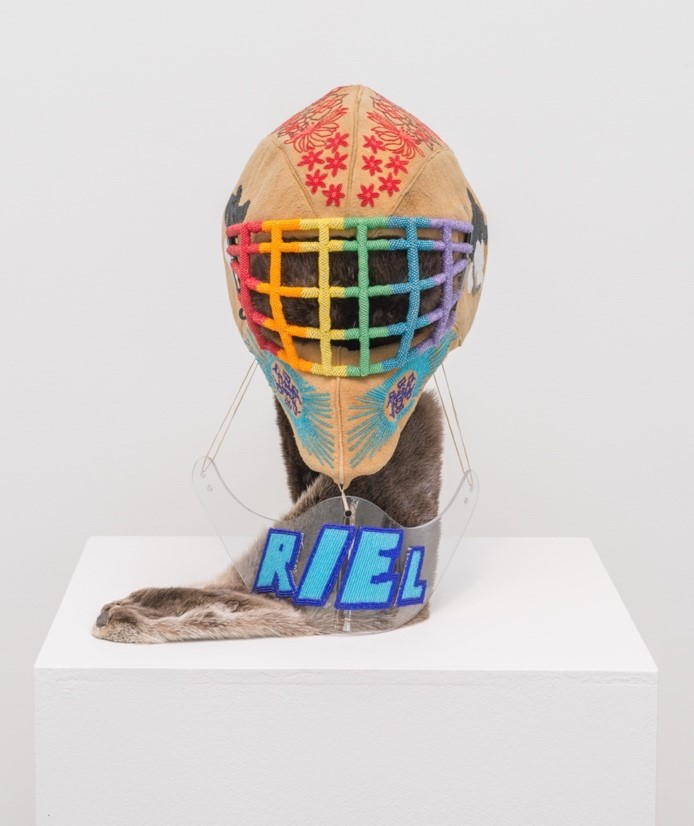 """An otter pelt extends down from a goalie mask and lays on a white plinth. Overtop is a clear Plexi glass neck guard with blue beaded letters that spell the name """"Riel"""". Above the pelt is an otter skin goalie mask with Indigenous flag imagery and red maple leaves. The face cage of the mask is beaded in rainbow colours. Two images of this sculpture are presented, showing a front facing view and an oblique angled view of the work"""