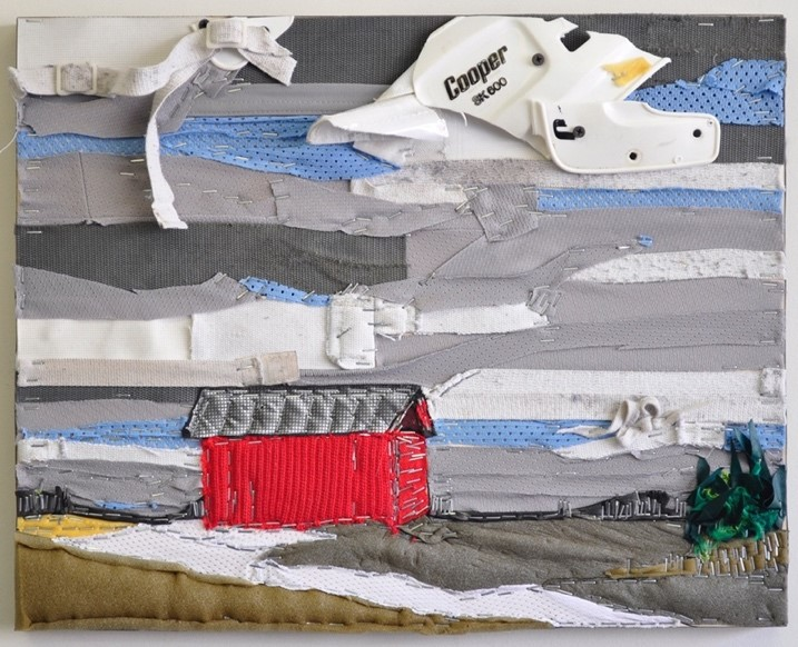 This recycled hockey equipment collage depicts a grey and blue textured sky (made from shoulder pads and jersey fabric) and a red barn in a field lightly covered in snow. The ground is created from the foam found inside hockey pads. Positioned on the field of a red barn with a grey roof and green trees on the far right of the piece.