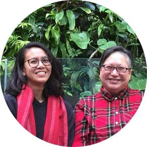 Artists Althea Balmes (she/her) and Jo SiMalaya Alcampo (they/them, siya), known together a Kwentong Bayan Collective, are smiling at the camera sitting side by side. On the left, Althea is wearing a red scarf that matches Jo's red shirt on the right. The artists are pictured in front of a background of lush green plant leaves. The picture is cropped into a circle.