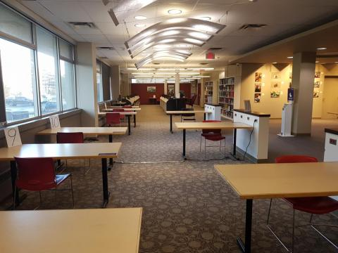 Series of study tables spaced out on main floor of library. Single chair at each table