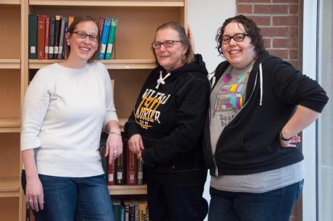 Three library course reserves staff smiling and standing in front of shelf of books
