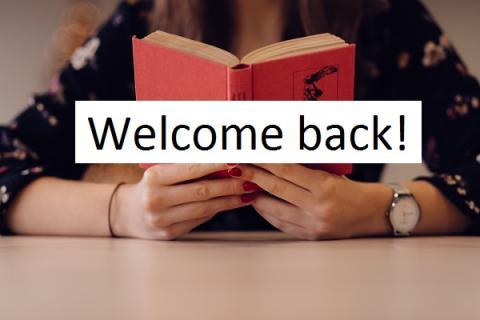 """Person holding open book. Words announce """"Welcome back!"""" and ask users to click to find out all you need to know this semester."""""""
